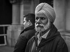 The Watching (Leanne Boulton) Tags: life street city uk light shadow portrait people urban blackandwhite bw white man black detail male texture monochrome face look canon beard 50mm mono scotland living blackwhite eyes natural emotion humanity bokeh outdoor expression glasgow candid character culture streetphotography streetlife scene depthoffield human shade portraiture 7d pensive feeling turban sikh society tone facial candidportrait candidstreetphotography