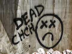 Dead Christchurch (Steve Taylor (Photography)) Tags: wood city shadow newzealand christchurch streetart brick art broken face wall dead graffiti earthquake sad grain demolition canterbury x nz quake damage southisland cbd smashed cracked plywood muted chch redzone 22february2011