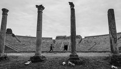 running the latest show (nzfisher) Tags: theatre 圆形剧场 amphitheatre ruins remains ancient roman roma rome column blackandwhite monochrome mono travel holiday running boy boyhood child 24mm canon ostiaantica lazio