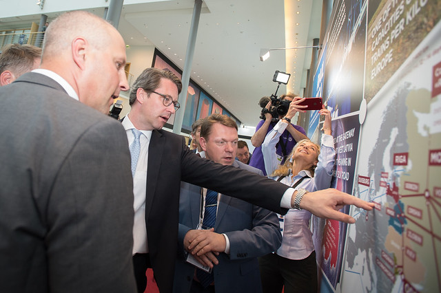 Andreas Scheuer poses a question to Edvins Berzins and Kaspars Ozoliņš at the Latvia stand