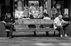 Personal Space (Anne Worner) Tags: anneworner blackandwhite silverefex bw bench candid man mannequin mono monochrome pavement people postcards storedisplay street streetphotography woman books bookstore storefront windows separate urban sitting reading torgalmenningen bergen norway candidstreetphotography naturallight daylight