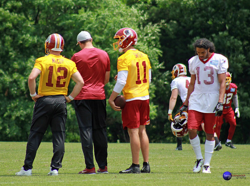 Redskins QB's Colt McCoy (12) and Alex Smith (11) talk to coach during practice.