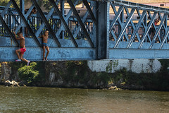 Hanging from the bridge (Adrià Páez) Tags: hanging from bridge water river douro portugal europe oporto porto o city kids boys children street streetphoto streetphotography people blue s swimming suit