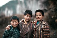 Bhutan: The Three Friends. (icarium.imagery) Tags: bhutan buddhist canonef85mmf12liiusm canoneos5dmarkiv captureone drukyul children boys gasa warmlook earthy himalaya moody naturallight portrait three rural street traditionaldress festival friends sundaylights