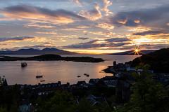 Oban Sunset (Kaua'i Dreams) Tags: oban scotland sunset mccaigstower clouds sky water harbor ferry mountains sun rays sunburst uk unitedkingdom