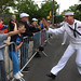A Sailor high-fives a child during the Staten Island Fleet Week Memorial Day Parade.