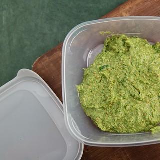 Pistachio pesto in a plastic food container .
