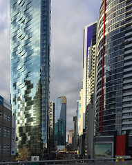 Melbourne at sunset (Marian Pollock) Tags: australia victoria melbourne skyscrapers reflections city street windows architecture buildings clouds sunset signs highway hotel utrbancentral eurekatower iphone