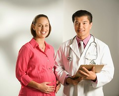 Doctor and pregnant woman. (perfectionistreviews) Tags: indoors color horizontal 4045years attractive asian business doctor health illness job medical medicine man occupation physician profession professional whitecollar work healthcare caucasian women woman patient 3035years checkup examination exam prenatal gynecology obstetrics pregnancy pregnant halflength eyecontact happy smiling smile wellness midadult youngadult hispanic