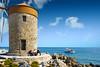 Windmill (mirsavio) Tags: rhodes greece fujifilmxt windmill sky clouds boat people quay stones