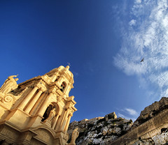 Modica ispirazione.. (Robyn Hooz) Tags: modica sicily ispiration ispirazione chiesa duomo italia tramonto sicilia bird uccello nuvole blu case