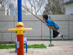 On the swing in Pyongyang, North Korea (TeunJanssen) Tags: pyongyang northkorea korea dprk asia ypt youngpioneertours playing playground swing kid girl travel traveling worldtravel backpacking olympus omd omdem10