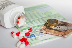 """Extra NHS Funding... where from and how to pay for it ?"" (Ian Johnston LRPS) Tags: nhs medical drugs cost prescriptions pills money coins pounds funding increase onwhite indoors comment editorial redandwhite capsules bottle open extra political"