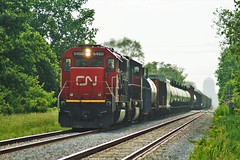 A Look Down the Horizon (Ontario Trackside Photography) Tags: cn train trains railfanning canadian national 438 windsor ontario chatham subdivision railroad sky zone haze distant zoom city tracks sd60 5450