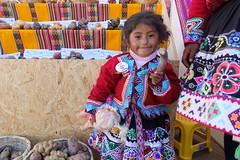 A young girl holds a native potato at her mother's stall at the World Potato Congress in Cusco, Peru. Photo: Holly Holmes/RTB