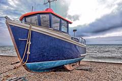 Sea Otter (Geoff Henson) Tags: boat fishing sky clouds sea beach shingle blue red rope knots waves