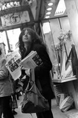 111770 31 (ndpa / s. lundeen, archivist) Tags: nick dewolf nickdewolf photographbynickdewolf blackwhite bw monochrome blackandwhite 35mm film boston massachusetts november 1970 1970s citylife streetlife streetphotography candid people city downtown woman youngwoman brunette longhair t mta mbta charlie subwaystation sign signs newspaper undergroundnewspaper phoenix thephoenix newspapers bag backpack vendor selling business store shop window displaywindow sidewalk