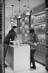 melbourne-0271-ps-w (pw-pix) Tags: man woman boy girl talking discussing standing leaning counter shop interior shelves lights sign jars display asian nocameras nophotos reflections tiles wood cupboards door doorway lookingin glass street bw blackandwhite monochrome people urban city bourkestreet cbd melbourne victoria australia peterwilliams pwpix wwwpwpixstudio pwpixstudio