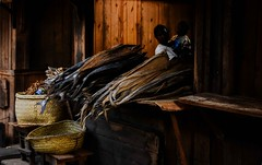 Dried Fish and Eel (Rod Waddington) Tags: africa african afrique afrika madagascar malagasy dried fish eel market stall woman baby child culture cultural indoor basket timber wooden wood