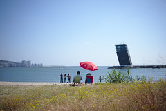Sunny Sunday plan for some: sitting by the sea side by side #portugal #fujixe2 #t3mujinpack (t3mujin) Tags: summer oeiras places red activity object ocean street architecture sitting umbrella atlantic location yellow color tower water beach city season portugal sand couple europe people sea estremadura