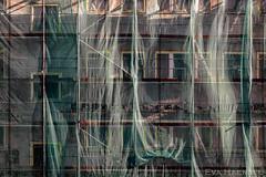 House under a veil (Eva Haertel) Tags: eva haertel haus house fassade facade baugerüst scaffolding baustelle buildingsite netz net grün green sonne sun schatten shadow struktur structure muster texture wind alt old renovieren renovate detail canon d600