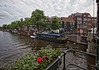 Amsterdam. (alamsterdam) Tags: amsterdam brouwersgracht canal water architecture bridge houseboats sky clouds bikes cars people urinal flowers