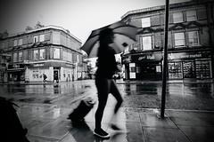 IMG_8219 (JetBlakInk) Tags: umbrella raining rain mono streetscene streetphotography baglady travelbag lowkey silhouette wideangle