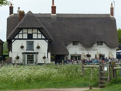 Only Pub IN a Stone Circle (Marit Buelens) Tags: path uk england wiltshire avebury fz200 thatch thatchedroof pub theredlion stonecircle standingstones haunted ghost tudor flowers straw roof