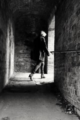 Assignment. (ianmiller6771) Tags: streetphotography blackwhite monochrome woman blonde alley bricks fuji 27mm mood dark candid bw brickwork leadingline ukstreetphotography streetphotographyuk shadows lightanddark