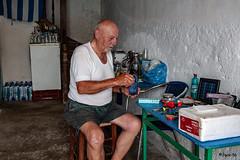 _DSC5667 - Ce vieux pêcheur voyant que j'écoutais toutes les chansons grecques qui émanaient de sa maison,  m'a offert des chaises dans son entrée pour que nous profitions de sa musique. La pêche est mauvaise car les gros bouffent les petits. (Jack-56) Tags: kastelorizo pêcheur grec musiquegrecque grèce greece