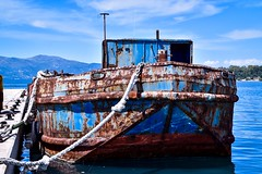 New rope, rusty boat. (rustyruth1959) Tags: whhelhouse superstructure ripples trees mountains rot neglected rustyboat ioniansea blue sea water quayside quay harbour ropes mooringrope rope bow hull hulk wreck rust rusty barge boat berth mooring port oldport corfu corfutown greece europe tamron16300mm nikond5600 nikon