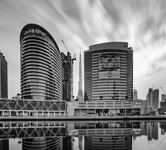 Reflection of the Business Bay... (Aleem Yousaf) Tags: bay style happy new digital camera long cityscape day outside outdoor town april downtown dubai city morning light year zayed modrn hotel properties damac buildings architecture skyscrapers financial district middle east united arab emirates photo walk photography 2470mm exposure sky clouds drag monochrome longexposure mono tones burj khalifa tall cranes construction reflections tower blue poster projection national canal water waterfront