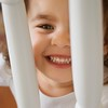 Stock Images (perfectionistreviews) Tags: square indoors color photograph oneperson 12years caucasian toddler female girl children child cute teeth mouth face eyecontact happiness happy smiling smile portrait banister railing rail home peeking childhood domesticscene kids youth person people onepersononly lifestyle closeup expression emotion