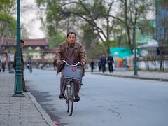 Cyclist on Sariwon Folk Customs Street, North Korea (TeunJanssen) Tags: folk customs street cyclist korea dprk northkorea youngpioneertours ypt travel traveling worldtravel worldtrip sariwon man olympus omd omdem10 backpacking 75mmf18