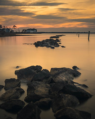 A dramatic landscape of a lake with rocks on the foreground and a big house on the background at sunset in Frankford, Delaware, USA. (pedferr) Tags: horizon sunny color nature lake 4x5 orange unitedstatesofamerica ocean outdoors skyline dramatic lines usa sunrise sunset shapes delaware vertical mystic rocks sun scene pattern warm yellow river backlight landscape texture park clouds longexposure sky house