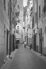 sbiadisce il tempo (fotomie2009) Tags: bn bw noli liguria italy italia monochrome monocromo monotone grey old man monopattino pushscooter scooter lamp lampione lampioni street