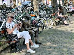 DSC_5859 Munsterplein / Platz vor der Munsterkerk / Münsterkirche in Roermond; dicht beieinander geparkte Fahrräder - Sitzbänke mit Bronzeskulpturen. (stadt + land) Tags: munsterplein platz munsterkerk münsterkirche geparkte fahrräder sitzbänke sitzbank bronzeskulptur niederlande roemond hansestadt hanse neuehanse fluss maas rur grenze deutschland einkauf outlet grenzstadt