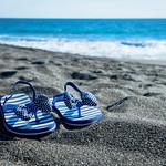 Girl's beach sandals on the sand thumbnail