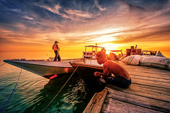 Sunset at Rajuni Island pier (syukaery) Tags: green sunset rajuni island takabonerate nationalpark humaninterest dailylife pier indonesia nikon nikkor 1635mm d750 activities dusk boats