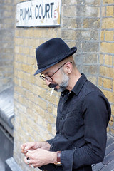 Cigarette Break (gooey_lewy) Tags: shoreditch london spittlefields market east end grad graduate fashion week street portrait photo people random pulled form stranger models model human touch toni guy barber hairdresser hat cigarette glasses tash mustache handlebar beard puma court sign road brick wall style work
