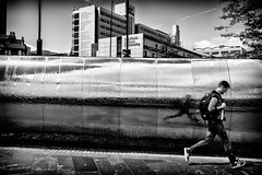 Stride (The Glass Eye) Tags: sheffield may 2015 station sculpture waterfeature university man running rucksack street panasonic gx7 olympus17mmf18