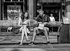 The Package and The Grinning Cat (Anne Worner) Tags: anneworner bergen blackandwhite norway silverefex torgalmenningen bw bench box candid couple man mono monochrome people purse sale sitting storefront stores street streetphotography sunglasses talking woman candidstreetphotography naturallight daylight