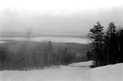 121269 33 (ndpa / s. lundeen, archivist) Tags: nick dewolf nickdewolf december photographbynickdewolf winter greenville maine mooseheadlake snow blackwhite bw 1969 1960s monochrome blackandwhite skitrip bigsquaw bigsquawmountain bigsquawmountainresort 35mm film skiing slopes trail run view lake trees