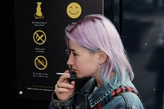 Smile. (ianmiller6771) Tags: girl smoking smile irony denimjacket colouredhair serious cigarette fuji 50mm ukstreetphotography candid colourfulhair tartan streetphotographyuk