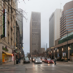 1974 continues to domineer & overbear a streetscape even yet, in the form of yon concrete banktower erected that year. (Tim Kiser) Tags: 16thstreet 16thstreetmall 16thandcalifornia 1970s 1970sarchitecture 1970sbuilding 1970sskyscraper 1974 1974architecture 1974building 1974skyscraper 2018 20180209 63317thstreet californiastreet cityandcountyofdenver colorado coloradofrontrange denver denvercolorado denverstreetscape february february2018 firstinterstatetowernorth frontrange img7935 jambajuice bank bankbuilding bankskyscraper banktower cars centralcolorado cloudy crosswalk downtown downtowndenver evening fog foggyevening headlights modernarchitecture modernistarchitecture modernistskyscraper overcast pedestrian pedestriansignal person signalizedintersection skyscraper skyscrapers stoppedataredlight stoppedtraffic street streetscape traffic treebranches