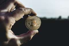 Miner holds bitcoin at dawn (ivan_volchek) Tags: bank banking business cash change closeup coin coins commerce currency dollar economy finance financial finger gold hand holding isolated metal money number one people savings sign two vintage wealth white