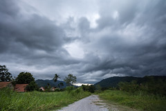 Storm clouds gather over Nakhon Nayok. (mikestewartinasia) Tags: path building asia nature southeastasia outdoor longexposure stormclouds trees road nakhonnayok house sky architecture cloud sarika skyline thailand clouds outside tree