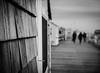 Bokeh, shadows and texture (Rabican7) Tags: newengland massachusetts provincetown capecod bokeh bokehlicious blackandwhitephotography blackandwhite monochrome shadows figures dof port harbor texture wood cold tourist walkers creative photography