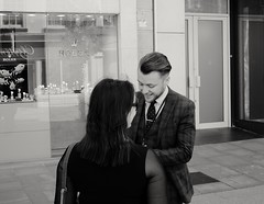 He talks like a jerk but he could eat you with a fork and spoon.  D.Bowie. (ianmiller6771) Tags: sharpsuit haircut conman blackandwhite bw monochrome streetphotography candid fuji 35mm spottedtie salesman smile victim unwary whiteshirt