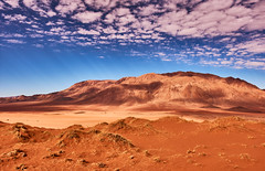 Play of colors of the desert (flowerikka) Tags: clouds desert dryclimate dune dünen dunes gräser hill landscape mountains namib namibdesert namibnaukluftnationalpark namibrand namibia nature redcolor sand sky sun valley view
